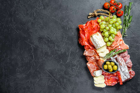 Italian antipasto, wooden cutting board with prosciutto, ham, parma, goat and Camembert cheese, olives, grapes. antipasti. Black background. Top view. Copy space.