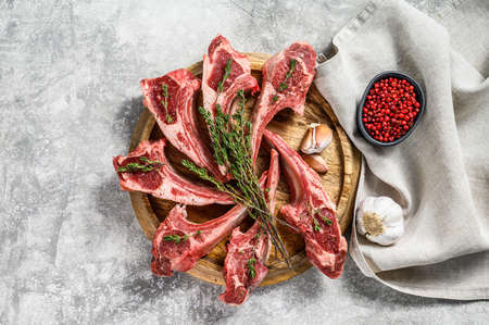 Rack of lamb , raw meat with bone, chops with salt, pepper. Gray background. Top view.