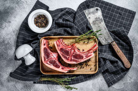 Raw fresh lamb meat on bones with rosemary and spices. Gray background. Top view.