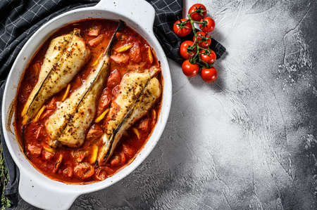 Cooking in tomatoes monkfish fish in a baking dish. Fresh seafood. Gray background. Top view. Copy space.