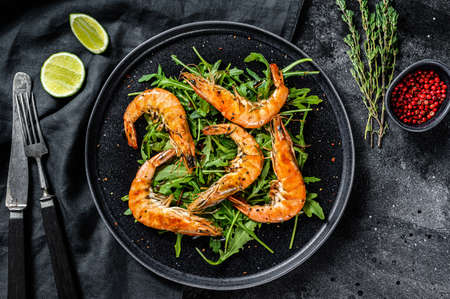 Salad with grilled giant tiger shrimps, prawns and arugula. Black background. Top view. Stock Photo