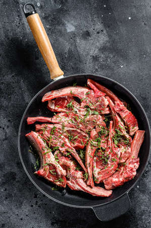 Raw fresh lamb rib chops marinated with thyme and mint in a pan. Black background. Top view. Copy space. Archivio Fotografico