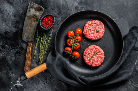 Raw Ground beef meat Burger steak cutlets in a pan. Black background. Top view. Archivio Fotografico