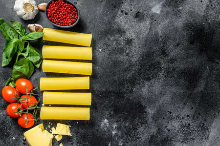 The concept of cooking cannelloni pasta. ingredients Basil, cherry tomatoes, Parmesan, garlic. Black background. top view. Copy space.