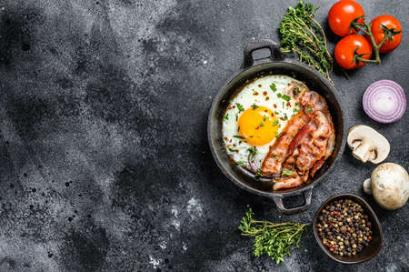 Pan of fried eggs with bacon and fresh tomato. Breakfast set. Black background. Top view. Copy space.