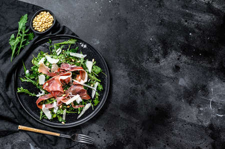 Salad with Parma, prosciutto ham, arugula and Parmesan. Black background, top view, space for text.