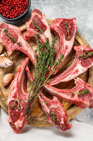 Rack of lamb , raw meat with bone, chops with salt, pepper. Gray background. Top view