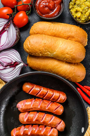 Ingredients for different homemade Hot Dogs, with fried onion, chili,, tomatoes, ketchup, cucumbers, and sausage. Black background. Top view