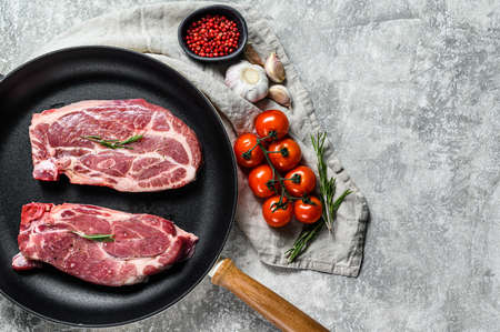 Fresh pork steak in a frying pan. Marbled farm meat. Gray background. Top view. Space for text.