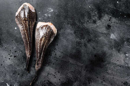 Fresh monkfish without a head. Black background. Top view. Copy space.