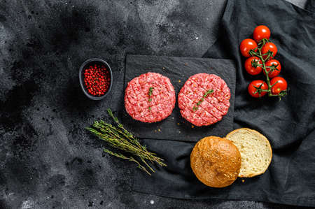 Recipe for burgers with marbled beef patties, cutlets. Black background. Top view.