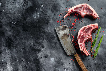 raw lamb chops fresh cut with meat cleaver. Black background. Top view. Copy space. Archivio Fotografico