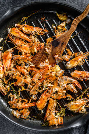 leftover shrimps, prawns in pan. waste food peeled, detail of the heads. Black background. Top view.