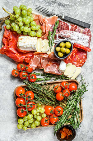 Italian antipasto, wooden cutting board with prosciutto, ham, parma, goat and Camembert cheese, olives, grapes. antipasti. Gray background. Top view. 写真素材