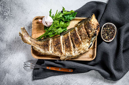 Baked whole fish haddock on a cutting Board. Gray background. Top view.