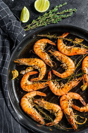 Grilled giant langoustine shrimps, prawns in a frying pan. Black background. Top view.