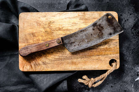 Vintage butcher meat cleaver on concrete board. Black background. Top view