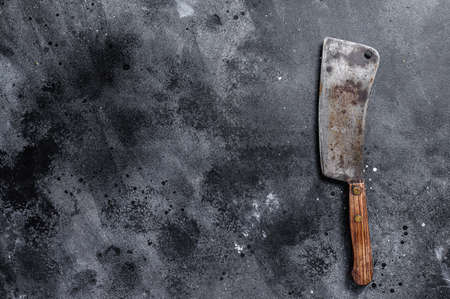 Vintage butcher cleaver with wooden handle. Black background. Top view. Copy space