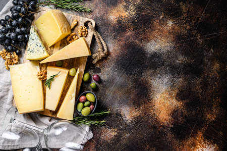 Collection of swiss, holland, french, italian cheeses with nuts and grapes. Dark background. Top view. Space for text