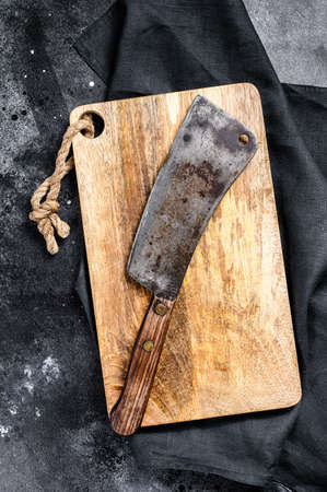 Meat cleaver on old scratched wooden cutting Board. Dark background. Top view 스톡 콘텐츠