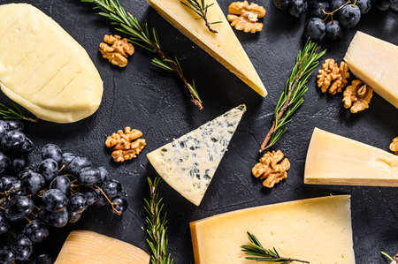 Beautiful background with Different types of delicious cheese, walnuts and grapes. Top view.