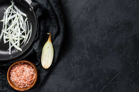 Sliced shallot in a pan, cooking fried onions. Black background. Top view. Space for text.