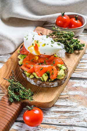 Salmon and Poached egg on grilled toast. White wooden background. Top view. Banque d'images