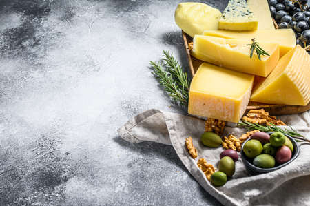 Cheese plate served with grapes, crackers, olives and nuts. Assorted delicious snacks. Gray background. Top view. Space for text.