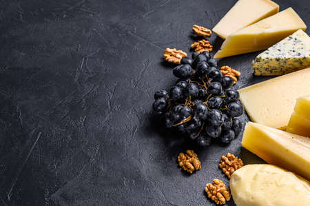 Different types of delicious cheese. Black background. Top view. Space for text.