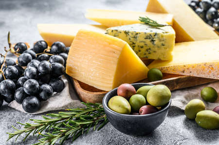 Cheese plate served with grapes, crackers, olives and nuts. Assorted delicious snacks. Gray background. Top view.