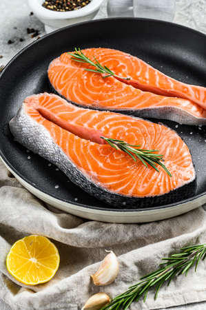 Raw trout steak in a frying pan. Healthy seafood. Gray background. Top view Archivio Fotografico