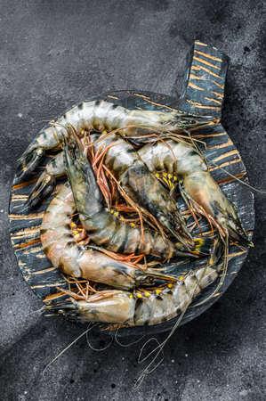 Black raw tiger prawns on black background. Top view. Reklamní fotografie