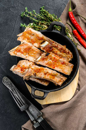 Delicious spicy marinated grilled spare ribs BBQ on Black background. Top view. Reklamní fotografie