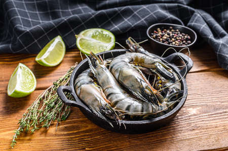 Fresh tiger shrimps, prawns with spices and herbs in a pan on wooden background. Top view.