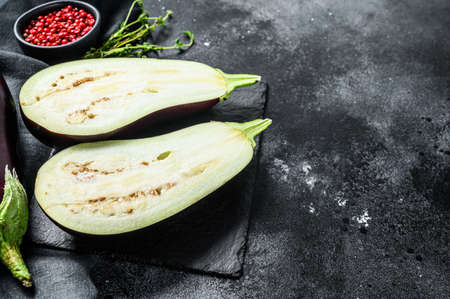 Sliced eggplant. Raw organic vegetables on Black background. Top view. Copy space