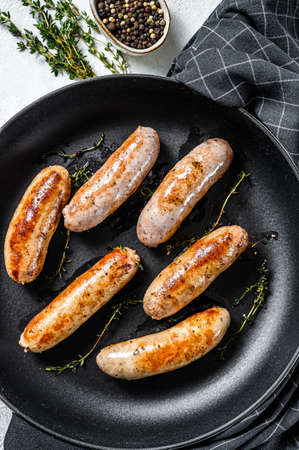 Tasty homemade sausages in a pan. Pork, beef and chicken meat. Gray background. Top view.