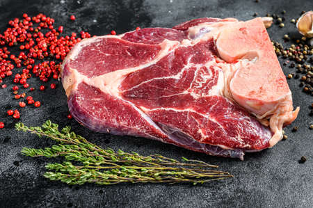 Raw beef shank with spices and herbs. Black background. Top view.
