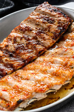 Spicy hot grilled pork spare ribs from BBQ served in a pan. Gray background. Top view. Archivio Fotografico