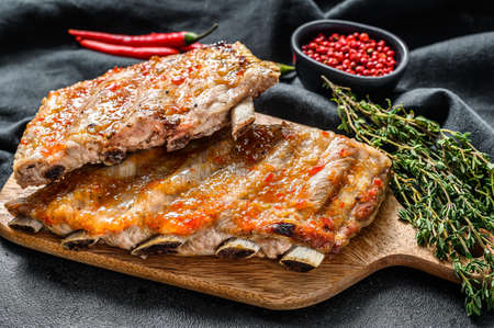 Spicy hot grilled pork spare ribs from BBQ served on cutting board. Black background. Top view.