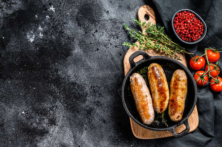 Tasty homemade sausages in a skillet. Pork, beef and chicken meat. Black background. Top view. Copy space. Reklamní fotografie