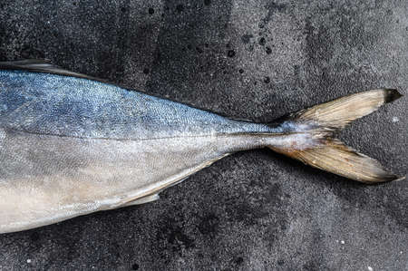 Fresh whole raw Japanese yellowtail. Fish Amberjack. Black background. Top view.