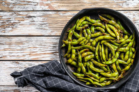 Cooked green edamame soybeans in a pan, japanese food. White background. Top view. Copy space. Reklamní fotografie