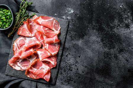 Coppa, Capocollo, Capicollo meat popular italian antipasto food. Black background. Top view. Copy space.