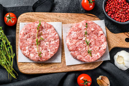 Raw pork cutlets, ground meat patty on a cutting Board. Organic mince. Black background. Top view.