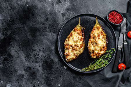 Baked eggplant with ground beef and cheese. Black background. Top view. Copy space.