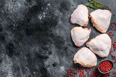 Raw chicken thigh with skin, organic meat. Black background. Top view. Copy space. Reklamní fotografie