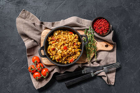 Fried Rice with Vegetables and eggs. Chinese Cuisine. Black background. Top view.