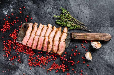 Grilled sliced pork steak on a meat cleaver. Organic meat. Black background. Top view. Reklamní fotografie