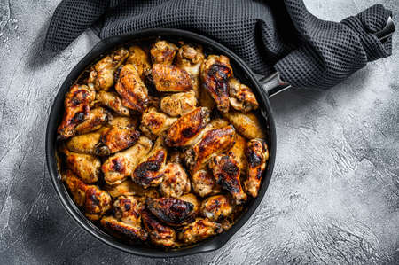 Barbecue chicken wings in honey sauce. BBQ poultry meat. White background. Top view. Copy space. Reklamní fotografie