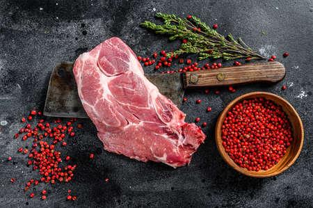 Raw pork marbled steak on a meat cleaver. Black background. Top view. Reklamní fotografie